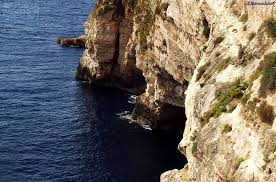The blue Mediterranean Sea with Ghar Hassan cave set in the sheer cliff