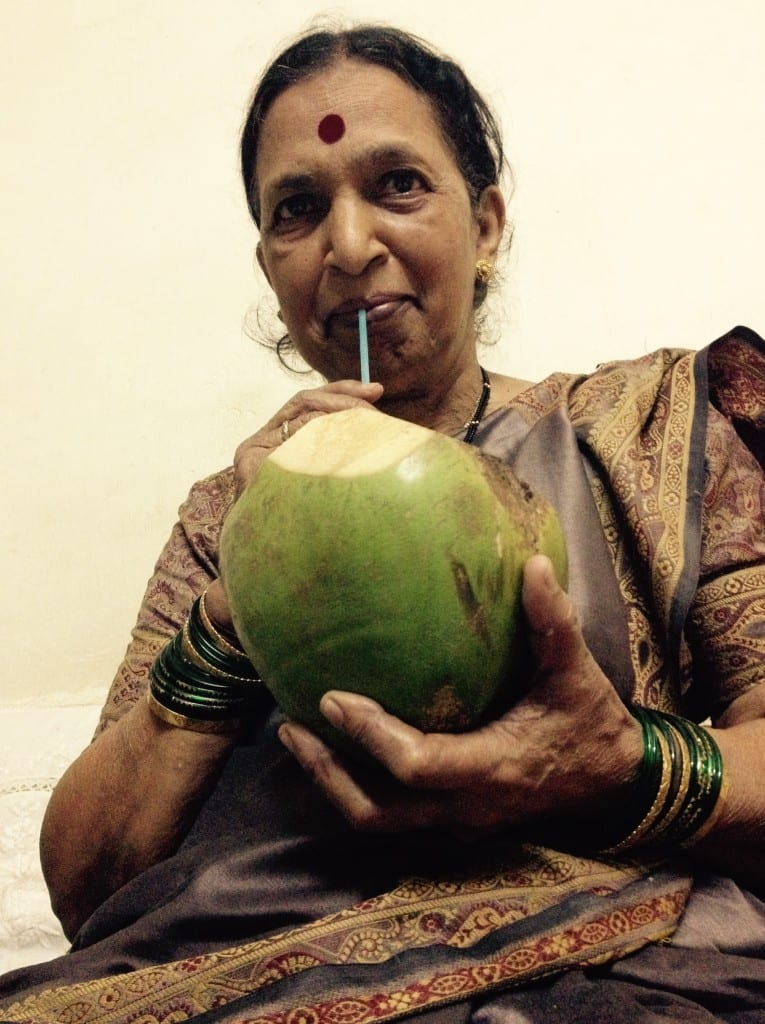 My mom sipping coconut water to cool herself