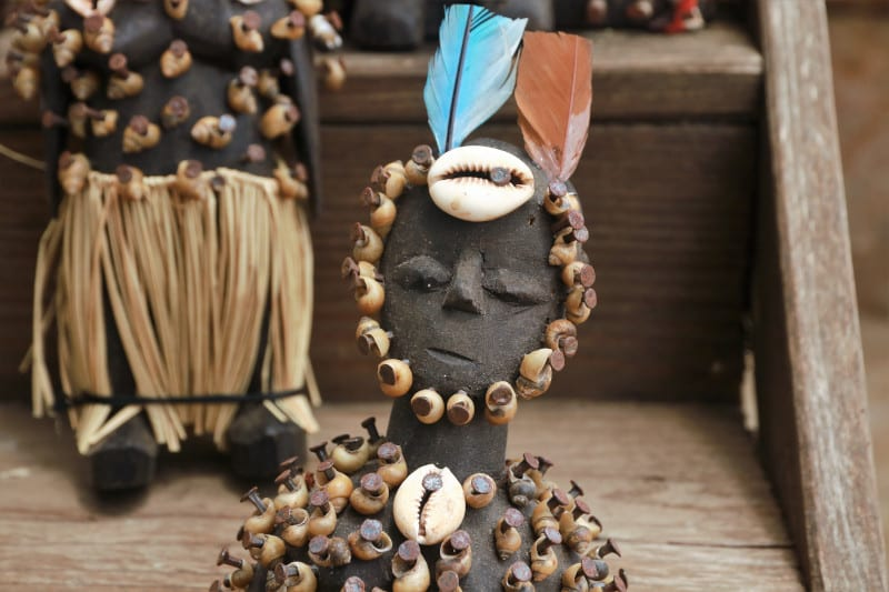 Wooden doll with shells and feathers