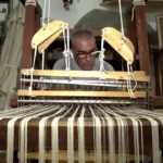 MalDia 01 22 01 20 Antoine Vella busily engrossed on his wooden spinning and weaving loom.