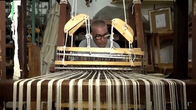 MalDia Antoine Vella busily engrossed on his wooden spinning and weaving loom