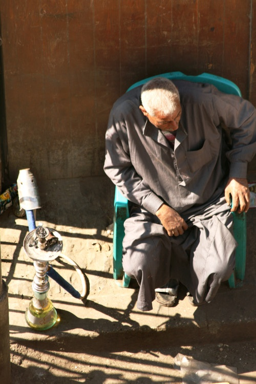 Local sitting next to a sheesha pipe Old Cairo
