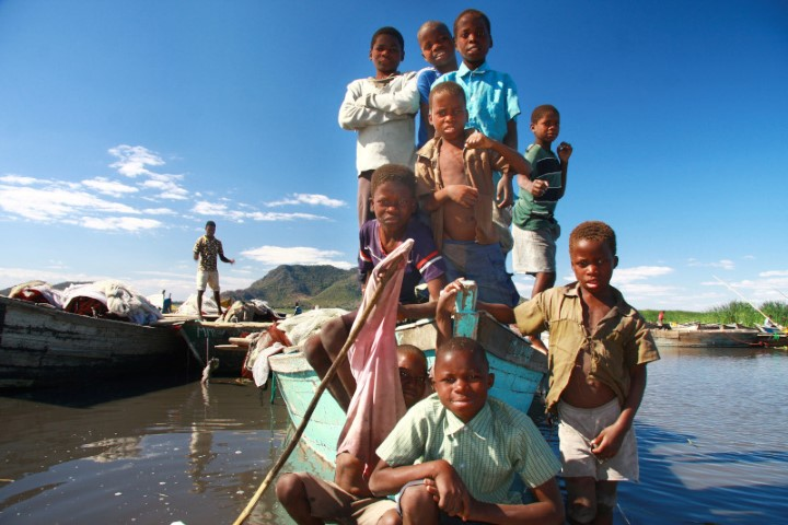 Children posing from inside a rowing boat at Kachulu village