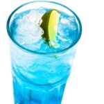 glass of blue cocktail with lime on white background SDRSh1u3fg